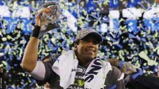 Quarterback Russell Wilson of the Seattle Seahawks celebrates with the Vince Lombardi Trophy after their 43-8 victory over the Denver Broncos in Super Bowl XLVIII