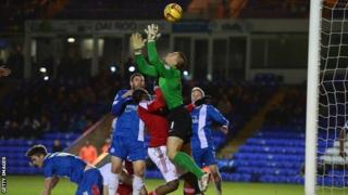 Bobby Olejnik of Peterborough United saves from Nile Ranger of Swindon Town