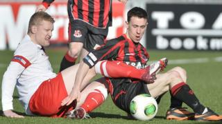 Ards defender David Armstrong and Paul Heatley of Crusaders battle for the ball in the match at Seaview