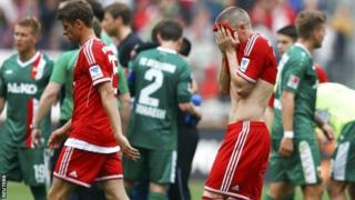 Bayern Munich's Bastian Schweinsteiger and Thomas Muller leave the pitch after their German Bundesliga match in Augsburg