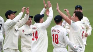 Glamorgan's fielders celebrate the fall of a Surrey wicket at the Oval