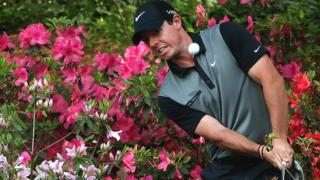 Rory McIlroy chips out of the azaleas at the 13th hole
