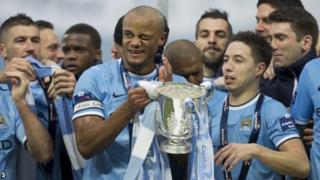 Manchester City players, including captain Vincent Kompany (holding trophy)