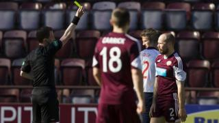 Hearts player Jamie Hamill is shown a second yellow card against Ross County