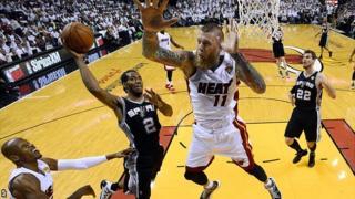 San Antonio Spurs forward Kawhi Leonard goes to the basket under pressure from Miami Heat forward Chris Andersen