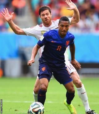 Swansea City midfielder Jonathan de Guzman fights off a challenge by Xabi Alonso in Netherlands' World Cup group game against Spain.