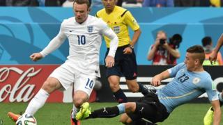 England's Wayne Rooney is challenged by Uruguay's Jose Maria Gimenez