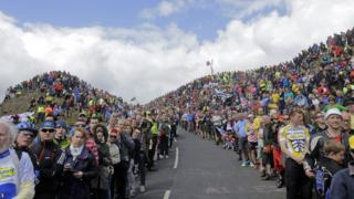 Spectators wait for the cyclists to climb Buttertubs pass during the first stage