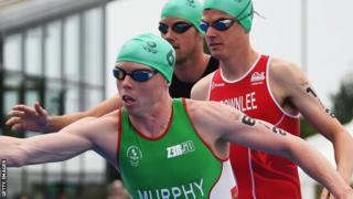 Conor Murphy of Northern Ireland waits to take over from Aileen Reid of Northern Ireland as Jonathan Brownlee of England looks on in the Triathlon Mixed Team event