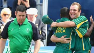 Prince Neluonde and Petrus Breitenbach celebrate South Africa's bowls triples victory as Northern Ireland's Neil Mulholland looks on