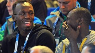 Bolt jokes with a friend at the netball