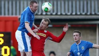 Kyle McVey beats Liam Boyce to the high ball while playing for Linfield