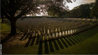 The setting sun creates long shadows in front of the graves at Sanctuary Wood Military Cemetery in Ypres, Belgium