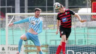 Warrenpoint's Jonathan Breen contends for the ball with Coleraine central defender David Ogilby