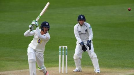 Durham batsman Keaton Jennings drives to the cover boundary, watched by Warwickshire wicketkeeper Tim Ambrose