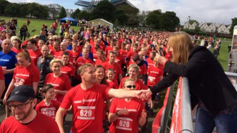 Runners shake the hand of Margaret Aspinall