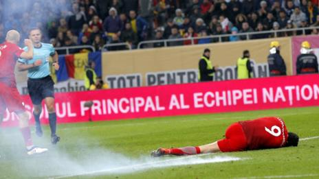Robert Lewandowski on the floor after flare explodes