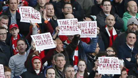 Arsenal fans hold up banners protesting against Arsene Wenger