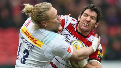 James Hook of Gloucester gets away from a tackle by Matt Hopper of Quins