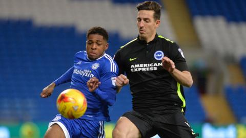 Lewis Dunk of Brighton battles for the ball with Cardiff's Kadeem Harris