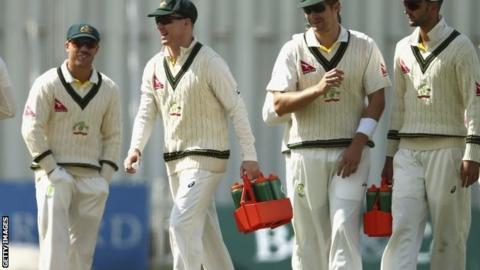 Australia's Chris Rogers (second left) carries drinks on to the field against Derbyshire
