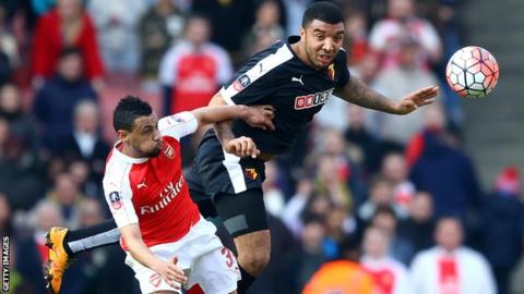 Troy Deeney of Watford beats Arsenal's Francis Coquelin to the ball