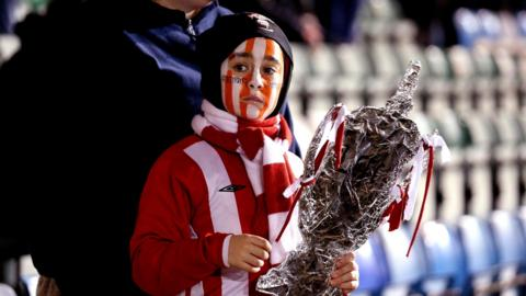 Lincoln City fan holds a homemade FA Cup trophy