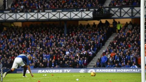 Rangers striker Kenny Miller collects objects that were thrown onto the pitch at Ibrox