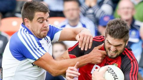 Drew Wylie of Monaghan challenges Down forward Connaire Harrison in the Ulster semi-final on 24 June