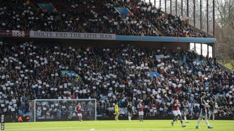 Villa fans stand to protest in the 74th minute