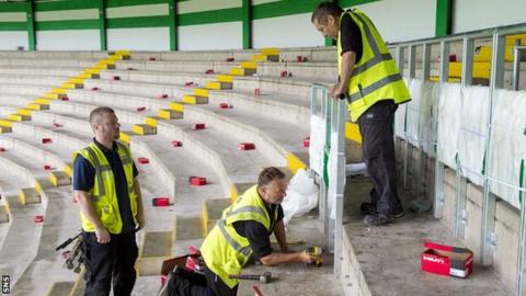 Workers install the new safe-standing barriers at Celtic Park
