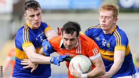 Two Tipperary players get to grips with Orchard forward Jamie Clarke at the Athletic Grounds