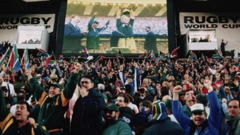 South African fans watch Francois Pienaar lift the trophy after South Africa defeated New Zealand in the Rugby World Cup final at Ellis Park, Johannesburg, 24th June 1995