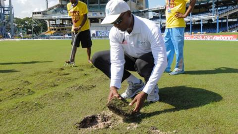 Umpire Gregory Brathwaite inspects the damaged outfield in Trinidad