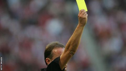 A referee showing a yellow card