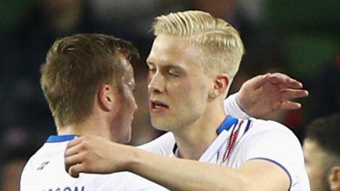Hordur Bjorgvin Magnusson (right) is congratulated by Aron Sigurdarson after curling in his free-kick