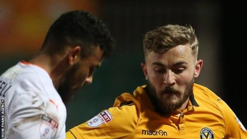 Newport's Dan Butler is tackled by Isaac Vassell of Luton Town