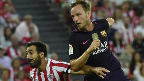 "Barcelona""s Ivan Rakitic, right, heads the ball to goal beside Athletic Bilbao's Mikel Balenziaga"