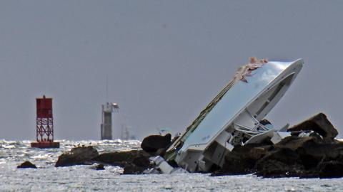 A boat lies overturned on a jetty, Sunday, Sept. 25, 2016, off Miami Beach, Fla.