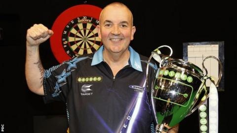 Phil Taylor celebrates after winning the inaugural Champions League of Darts