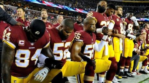 Members of the Washington Redskins kneel during the playing of the national anthem.