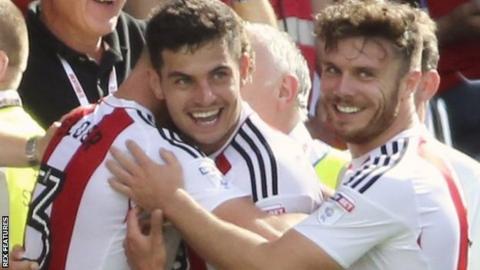 John Egan celebrates a goal for Brentford against Ipswich