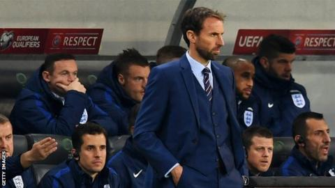 Gareth Southgate watches his England side as Wayne Rooney looks on from the bench