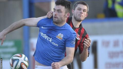Glenavon forward Eoin Bradley is challenged by Craig McClean of Crusaders