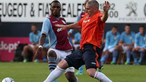 Christian Benteke is tackled by Steve McNulty on Villa's last visit to Kenilworth Road in a pre-season friendly in July 2013