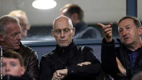 Bob Bradley checks his watch while watching Swansea under-23 alongside Alan Curtis and Huw Jenkins