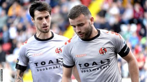 Declan Caddell congratulates Crusaders goal-scorer Colin Coates