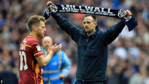 Millwall fans in front of a Bradford player