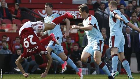 Rudy Gestede (left) goes tumbling the the Burnley area - no penalty though