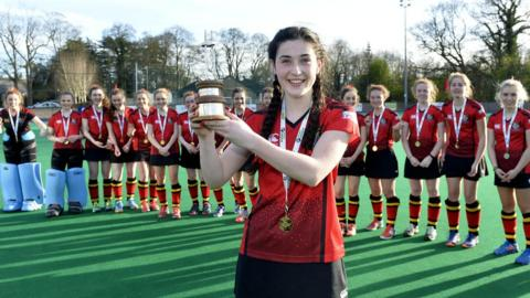 Captain Orla Thompson displays the trophy in front of her victorious Banbridge Academy team-mates